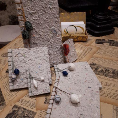 Carnet à reliure traditionnelle avec du papier recyclé fabriqué en atelier. Décor perles de papier et cuir.